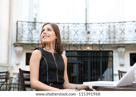 Young attractive businesswoman sitting in a luxurious coffee shop terrace with her laptop, smiling. - stock photo