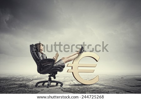Young attractive businesswoman sitting in chair and reading book - stock photo