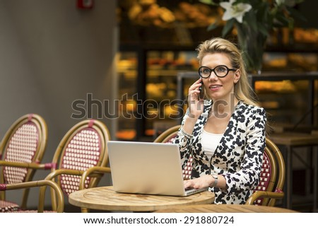 Young attractive businesswoman sitting outdoors with laptop and talking on a cell phone. - stock photo