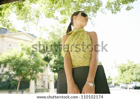 Young attractive businesswoman standing in the financial district wearing sunglasses and holding a folder in a tree lined street. - stock photo