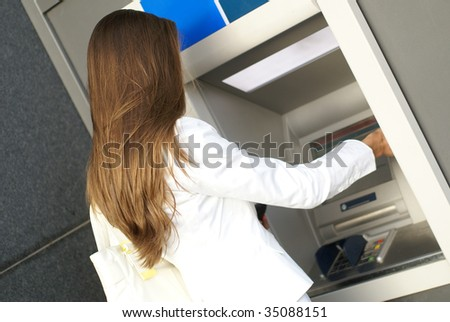 Young attractive businesswoman taking off money from the outdoor bank terminal - stock photo