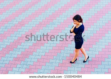 Young attractive businesswoman talking on phone while walking across the street - stock photo