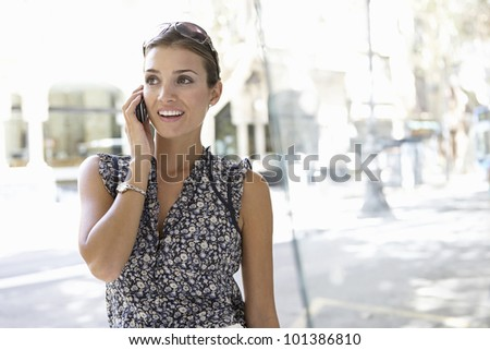 Young attractive businesswoman using a cell phone in the city.