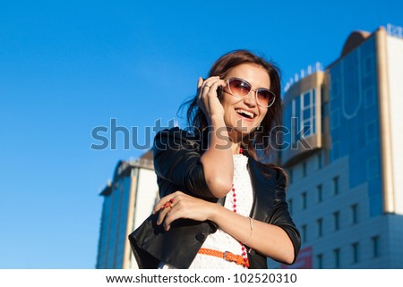 Young attractive businesswoman using a cell phone in the city - stock photo