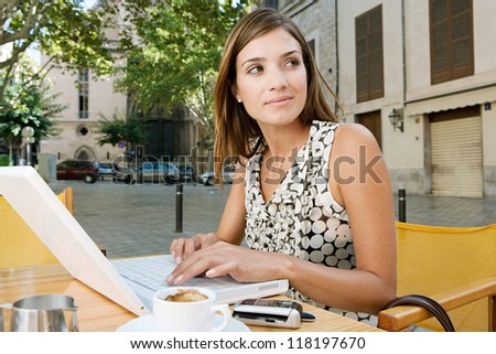 Young attractive businesswoman using a laptop computer and smiling while sitting at a coffee shop terrace in a classic city, outdoors. - stock photo