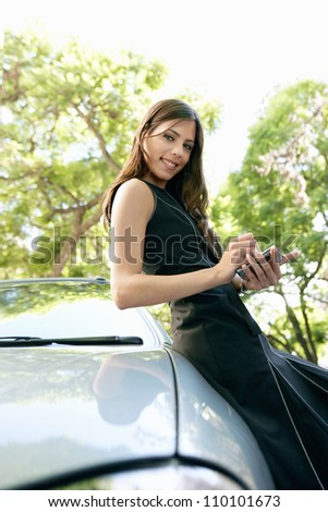 Young attractive businesswoman using a smart phone while leaning on a shiny car in a tree lined street.