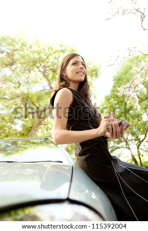Young attractive businesswoman using her smart phone while leaning on a car in a tree lined street, smiling.