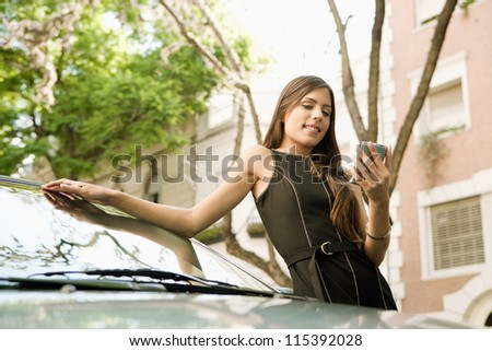Young attractive businesswoman using her smart phone while leaning on a car in a tree lined street, outdoors. - stock photo
