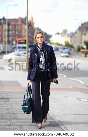Young attractive businesswoman walk on the pavement, city centre street shoot