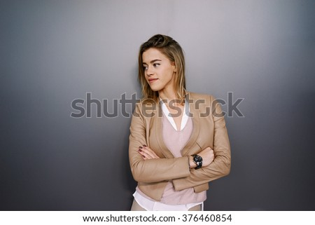 young attractive businesswoman with blonde hair posing on a gray background with copy space area for your text o design. - stock photo