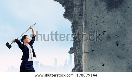 Young attractive businesswoman with hammer in hands