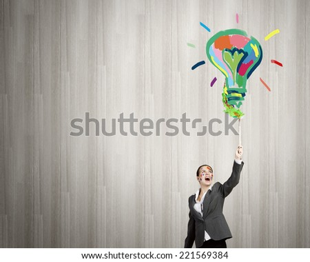 Young attractive businesswoman with paint brush in hand - stock photo