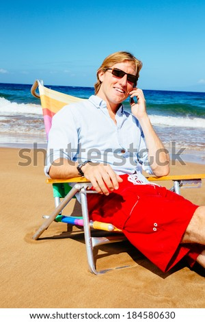 Young Attractive Casual Businessman Entrepreneur Relaxing at the Beach Talking on Cell Phone - stock photo