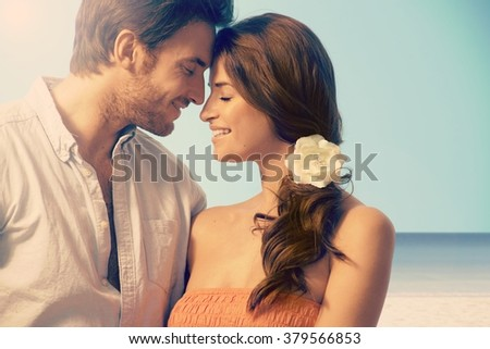Young attractive casual caucasian married couple having a romantic moment at the seascape beach. Eyes closed, touching, love, romance, flower in hair.