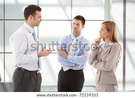 Young attractive casual office workers talking in hallway.?