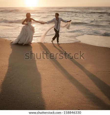 Young attractive caucasian bridal wedding couple walking along beach sunrise - stock photo