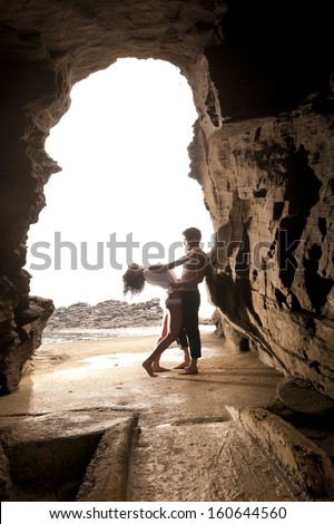 Young attractive caucasian couple dancing in rock archway at beach  - stock photo