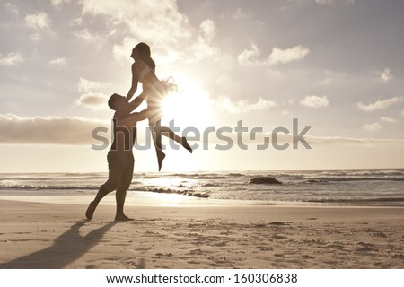 Young attractive caucasian couple dancing on beach at sunrise - stock photo