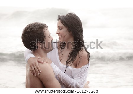 Young attractive caucasian couple flirting in surf - stock photo