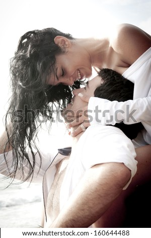 Young attractive caucasian couple flirting on rocks wearing white - stock photo