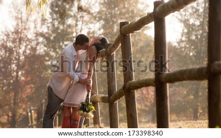 Young attractive caucasian couple flirting outdoors against wooden fence - stock photo
