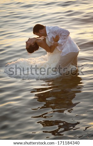 Young attractive caucasian couple flirting together in pool of water at sunrise