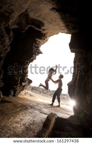 Young attractive caucasian couple jumping in rock archway - stock photo