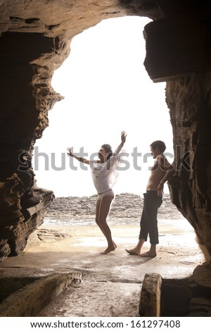 Young attractive caucasian couple jumping under rock archway - stock photo