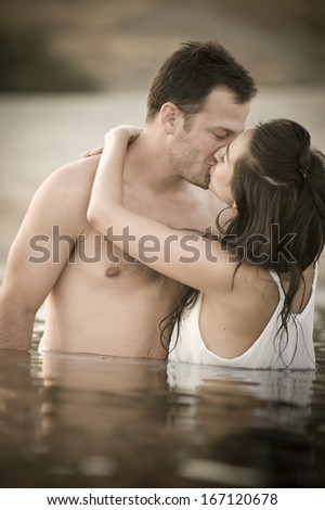 Young attractive caucasian couple kissing at the beach in water