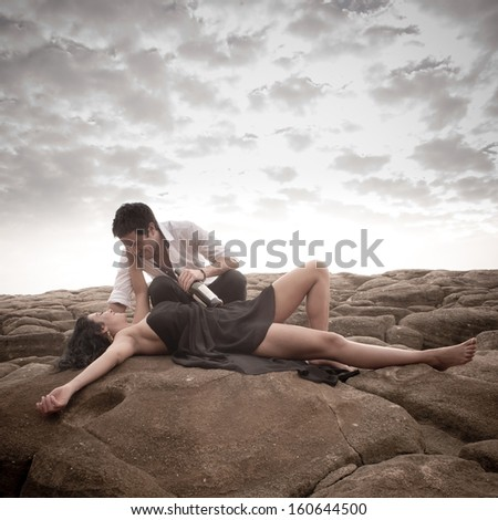 Young attractive caucasian couple kissing on rocks with clouds overhead - stock photo