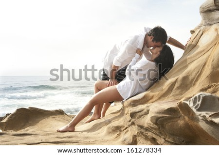 Young attractive caucasian couple leaning on rocks kissing by the beach wearing white - stock photo