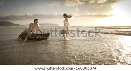 Young attractive caucasian couple playing in the surf with vintage bath tub