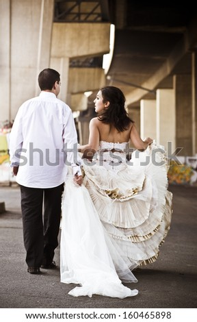 Young attractive caucasian couple walking under concrete bridge