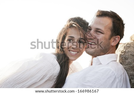 Young attractive caucasian couple wearing white and smiling together outdoors