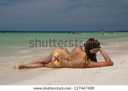 Young attractive caucasian girl lying on the tropical beach - stock photo