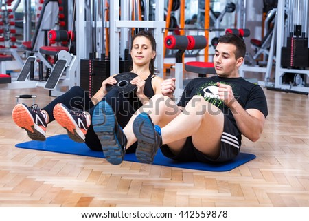 Young, attractive caucasian girl training her abs with a personal trainer at the gym on a mat, with sit- up exercise. - stock photo