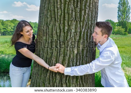 Young attractive caucasian man and woman in love holding hands around tree trunk - stock photo