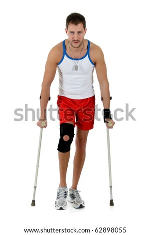 Young attractive caucasian man athlete on crutches, wearing a wrist brace and knee support,  bandaged. White background. Studio shot.