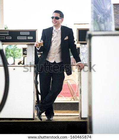 Young attractive caucasian man standing in dress suit leaning on gas pumps at filling station - stock photo