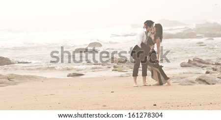 Young attractive caucasian standing together on misty beach