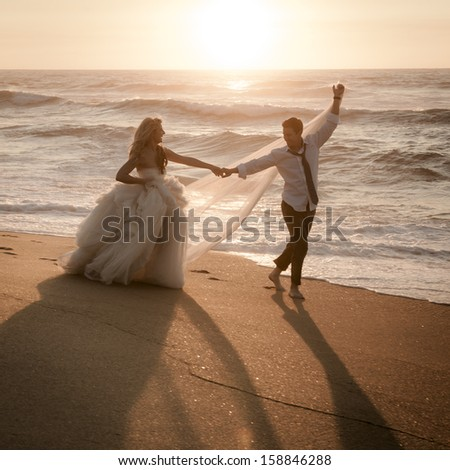 Young attractive caucasian  wedding couple dancing along beach - stock photo
