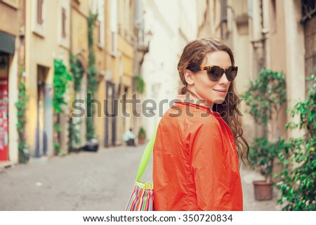 Young attractive cheerful woman walking in city  - stock photo