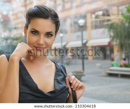 Young attractive cheerful woman walking in city, summer hot outdoor. - stock photo
