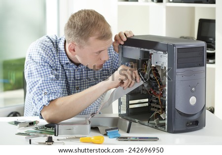 Young attractive computer specialist repairing computer in his office - stock photo
