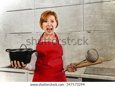 young attractive cook woman desperate in stress in apron holding cooking pot and rolling pin at home kitchen screaming frustrated and confused in lifestyle concept dirty grunge background edit  - stock photo