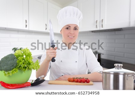 young attractive cook woman in uniform cooking salad in modern kitchen