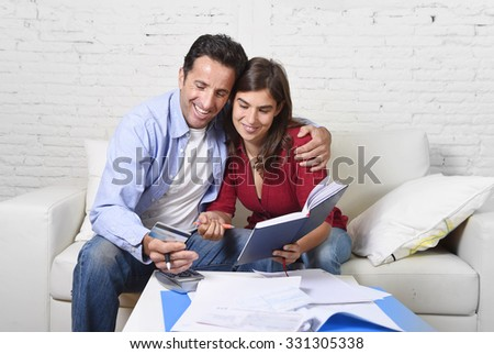 young attractive couple accounting at home couch with bank papers and documents, calculator and credit card living cost and mortgage expenses smiling happy in financial success and wealth - stock photo