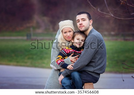 Young attractive couple and their cute little child, teenagers having fun outdoors, kissing and hugging - stock photo