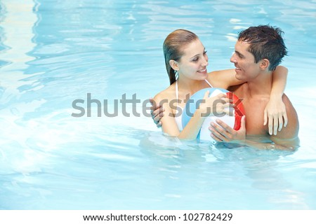 Young attractive couple bathing with beach ball in swimming pool