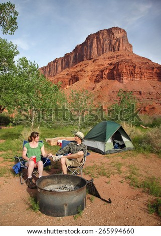 young attractive couple camping near red rock formation - stock photo